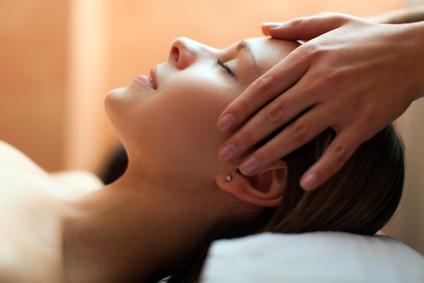 Kopf einer zufrieden-entspannten Frau, die gerade sanft an Stirn und Schläfen brührt wird.