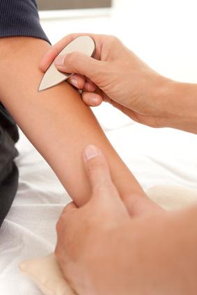 Unterarm eines Kindes, der mit einer tropfenförmigen Metallscheibe berührt wird.