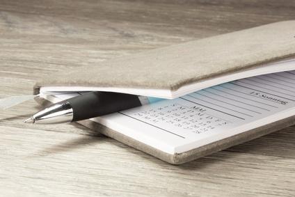 In braunen Wollstoff gebundener Terminkalender mit einem Stift zwischen den Seiten auf einem Holztisch