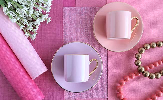 ピンクのテーブルの上にある1対のコーヒーカップとソーサー&丸まったランチョンマット