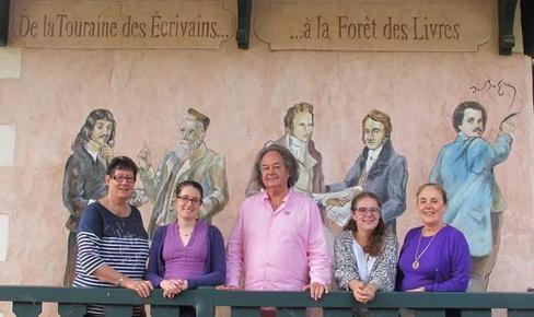Une partie des bénévoles de la Forêt des livres entoure Gonzague Saint Bris, devant la fresque des auteurs de Touraine que l'on doit à Armand Langlois, peintre à Amboise