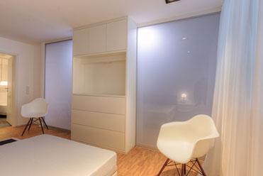 Regalsystem hinter Schiebetüren mit lichtdurchlässigem Glas