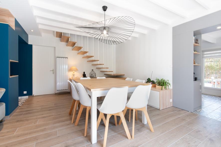 une espace de vie centré autour de la salle à manger souligné par les escaliers aériens