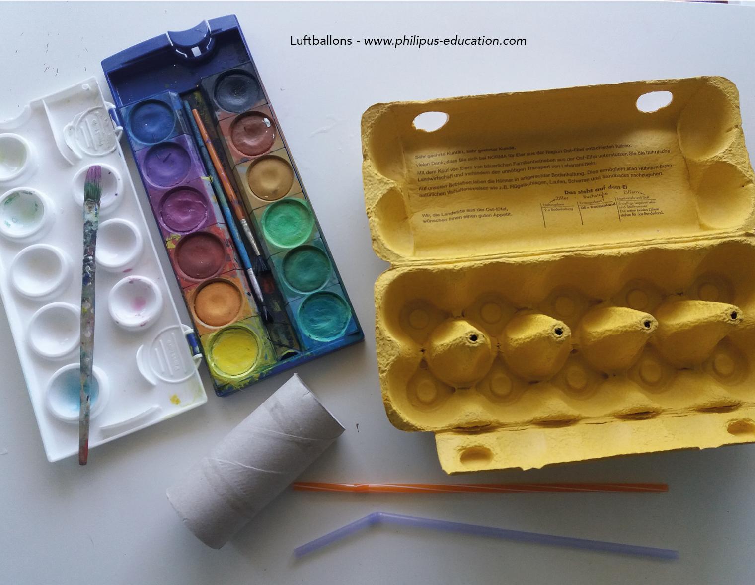 Wasserfarben, Toilettenrollen, ein Eierkarton mit spitzen Formen und Strohhalme