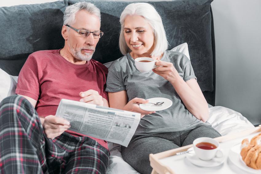 Älteres Ehepaar liest Zeitung im Bett.