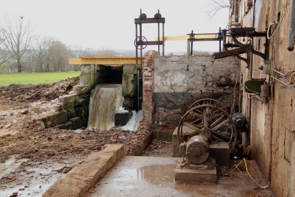 Das nun freistehende Vorgelege. Im Vordergrund der alte Generator. An der Wand der Motor zum Antrieb der Mühle bei Niedrigwasser. Auf den Konsolen an der Wand lag die Transmission zur Anpassung der Motor und Generator Drehzahl