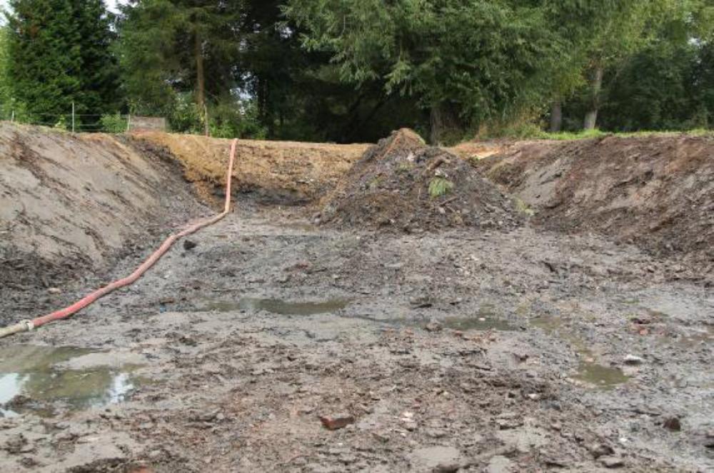 Eine Tauchpumpe hält im frei geräumten Kolk den Grundwasserspiegel flach. Der Damm wurde noch einmal erhöht, weil sich durch Setzungen die Krone abgesenkt hatte.