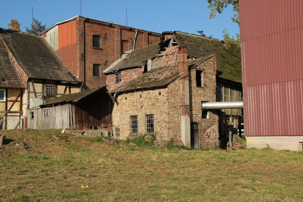 In dem Gebäude mit dem Schornstein war die Heizung für die Trocknung untergebracht. Dahinter, mit dem stark beschädigtem Giebel, die Reinigung. Mit Brettern verkleidet, die überdachte Wehranlage.
