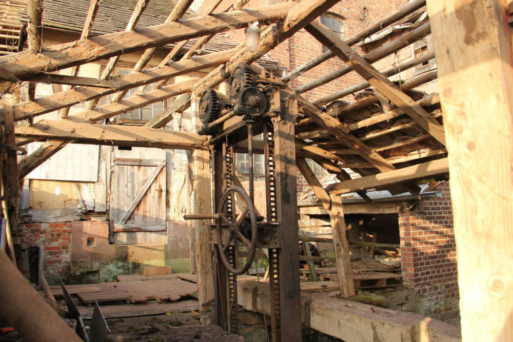 Der offene Wehrgang. Hinten rechts die Turbinenkammer mit ausgebautem Läufer. Die Tür in der Mitte führt direkt in die Mühle. Die Vorteile eines Dachs schätzt man spätestens wenn bei Hochwasser das frei stehende Wehr bedient werden muss.