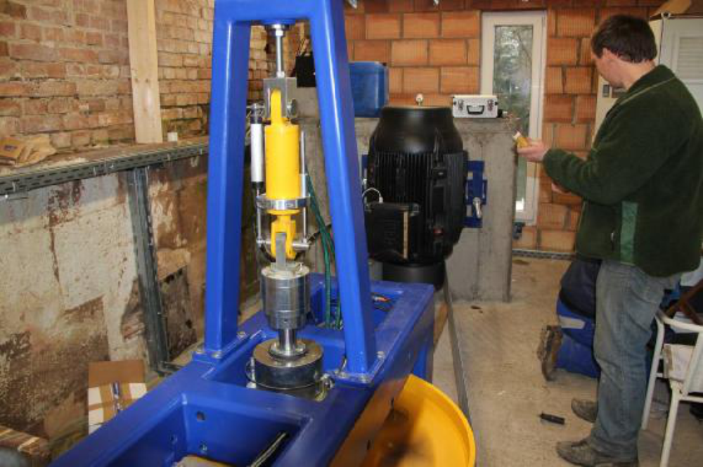Blick auf Turbine und Generator. Der gelbe Hydraulik Zylinder verstellt über das darunter angebrachte Steuerlager die Flügel des Laufrades. Unter dem Steuerlager ist das Traglager in der Traverse abgestützt.