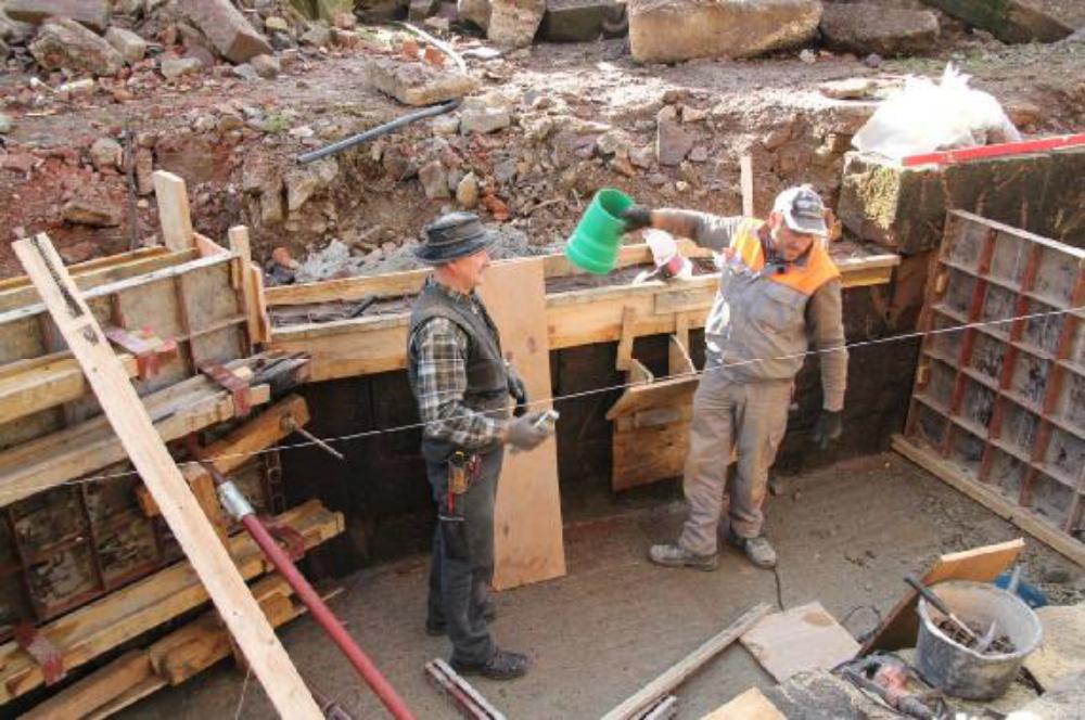 Das Aalrohr muss vor dem betonieren montiert sein. Kleine Einfülltrichter helfen den Beton auch hinter die verbliebenen Sandsteine zu bringen.