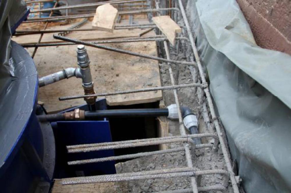 Der Sporn am Ende der Einlaufspirale. Die unter waagerechte Leitung ist die Deckel Entwässerung. Die verzinkte Leitung setzt das Führungslager unter Unterdruck und saugt eventuell eintretendes Wasser ab.