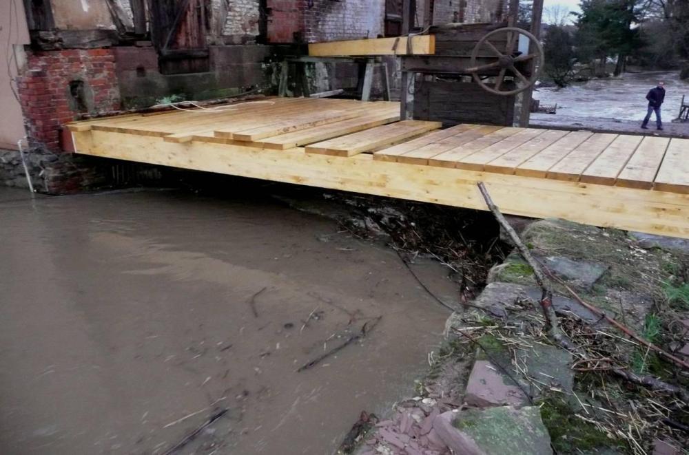 Die erste Hochwasserwelle ist da. Unmengen an Treibgut aus dem lange mehr oder weniger ungenutzten Mühlengraben drohen das Wehr zu verstopfen. Das gefährdet  massiv den gerade reparierten Deich und kann zu dessen Bruch führen.