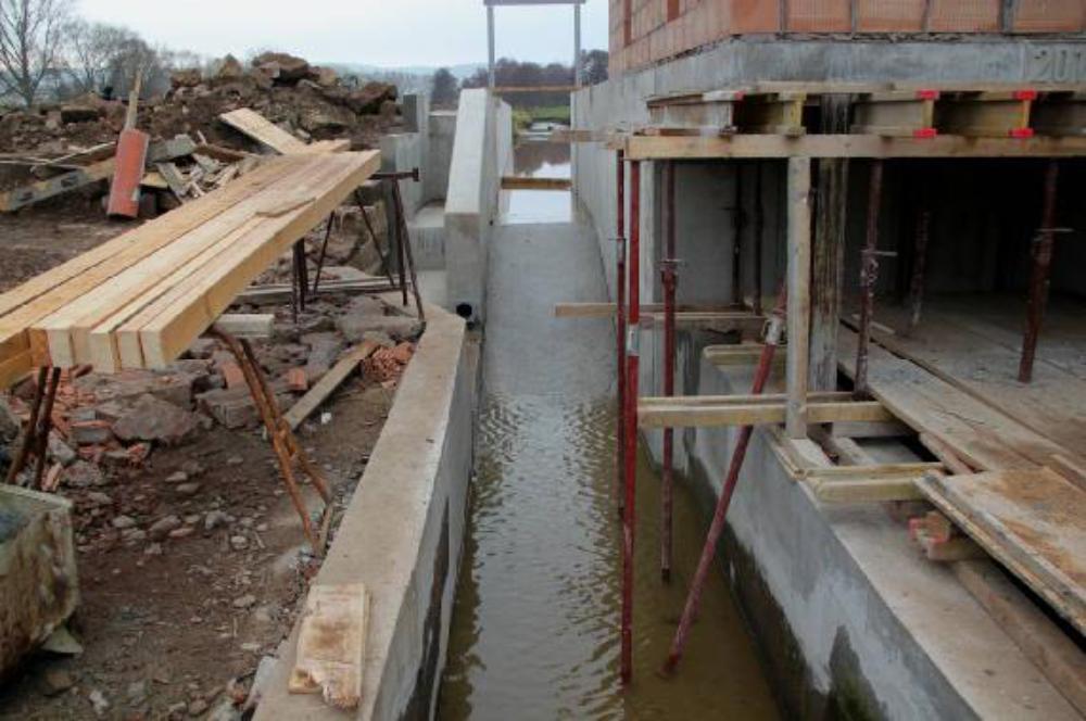Das Maschinenhaus steht noch auf der Schalung. Über den Leerschuss läuft der Mühlengraben ab. Das Bauholz für das Maschinenhausdach liegt bereit.