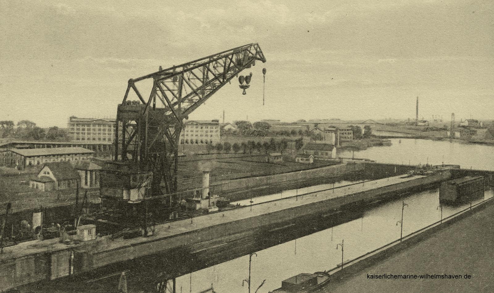 """Der """"Lange Heinrich"""" in der Südkammer. Im Hintergrund die 1919/20 gebauten Minenlagerhäuser an der 2. Einfahrt"""