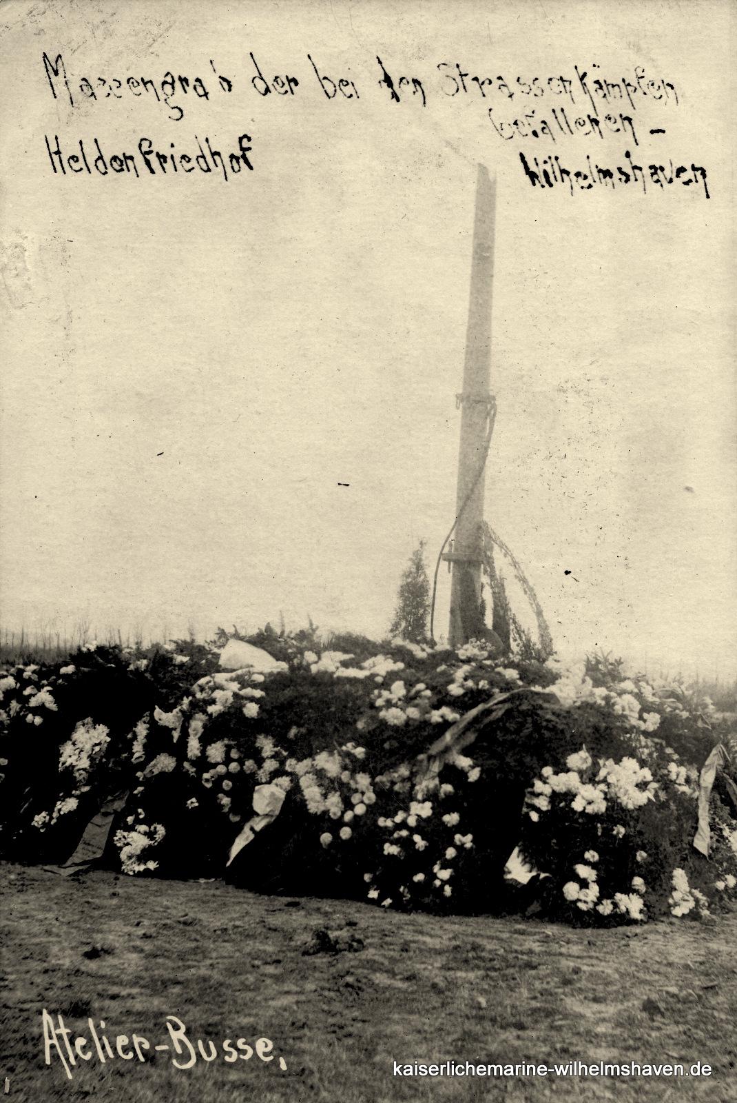 """Die wohl besser als Gemeinschaftsgrab zu bezeichnende Grabstelle auf dem Ehrenfriedhof, im Hintergrund der """"Lützow-Mast"""" (s. Ehrenfriedhof"""" unter Garnisonbauten/Friedhöfe)"""