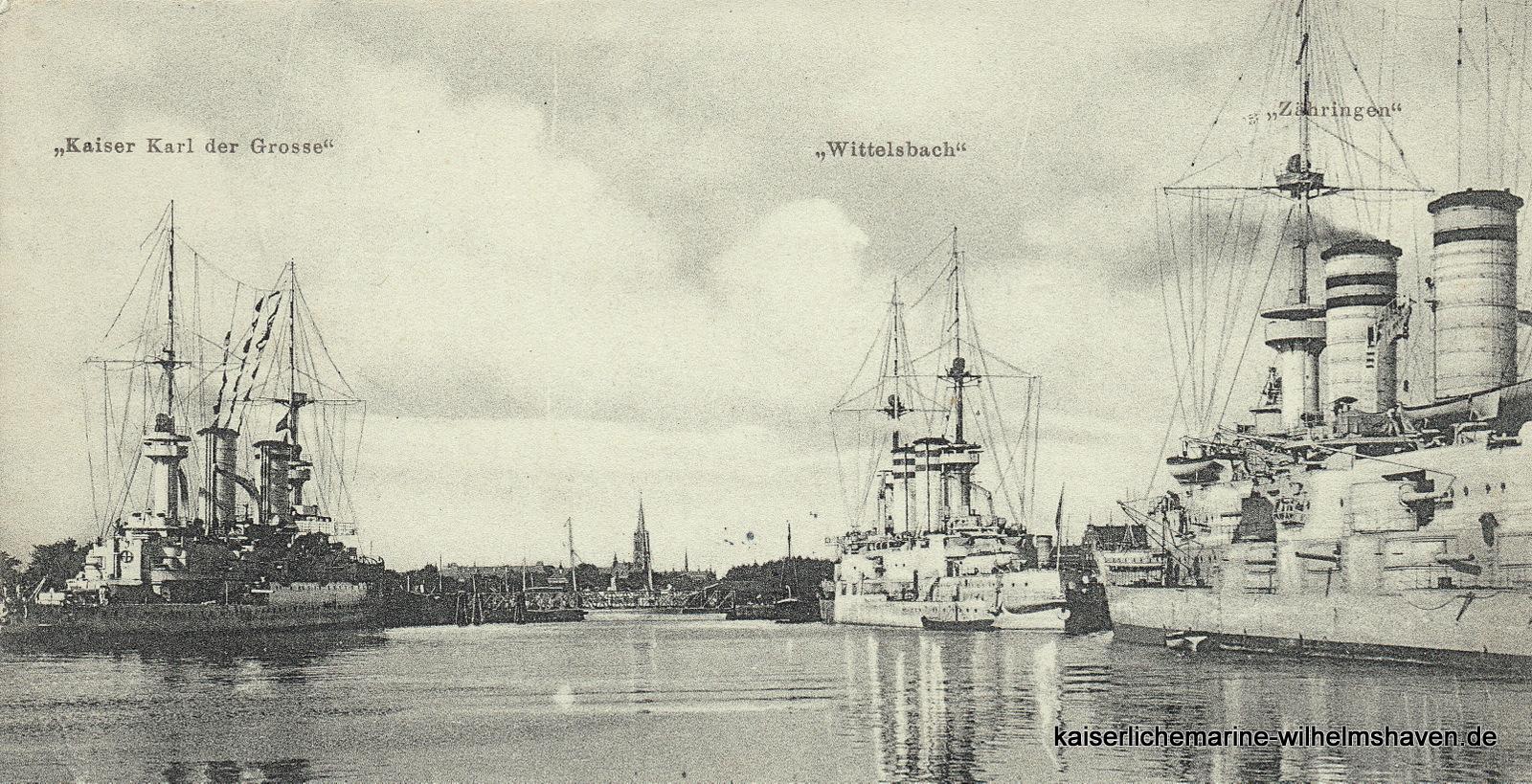 """SMS """"Wittelsbach"""" und Schwesterschiff SMS """"Zähringen"""" am Nordostkai, gegenüber am Nordwestkai SMS """"Kaiser Karl der Große"""". In der Bildmitte die Drehbrücke zur Schleuseninsel, ab etwa 1910 Hafeninsel, darüber die Petrus-Kirche"""