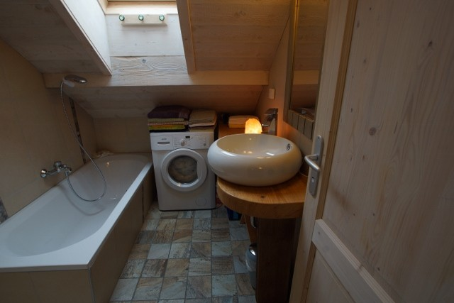 Badezimmer mit Badewanne, Dusche und Waschmaschine