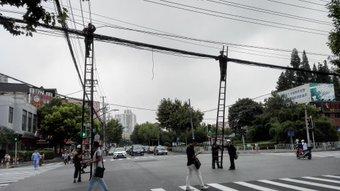路上の雑技。 上にいる人が下の人と呼吸を合わせないではしごが斜めになりながら自分で勝手に電線(?)を横移動する技がすごかった。後から下の人もはしごを移動してまっすぐに(写真ではわかりにくい。信号が青になると車が横を走る。水城路×仙霞路