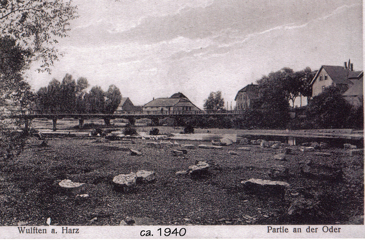 """Blick vom südlichen Ufer auf den Dreschmaschinenschuppen, das Haus Schülbe und rechts Bürohaus Gropengießer, damals """"Hotel zum Bahnhof"""""""