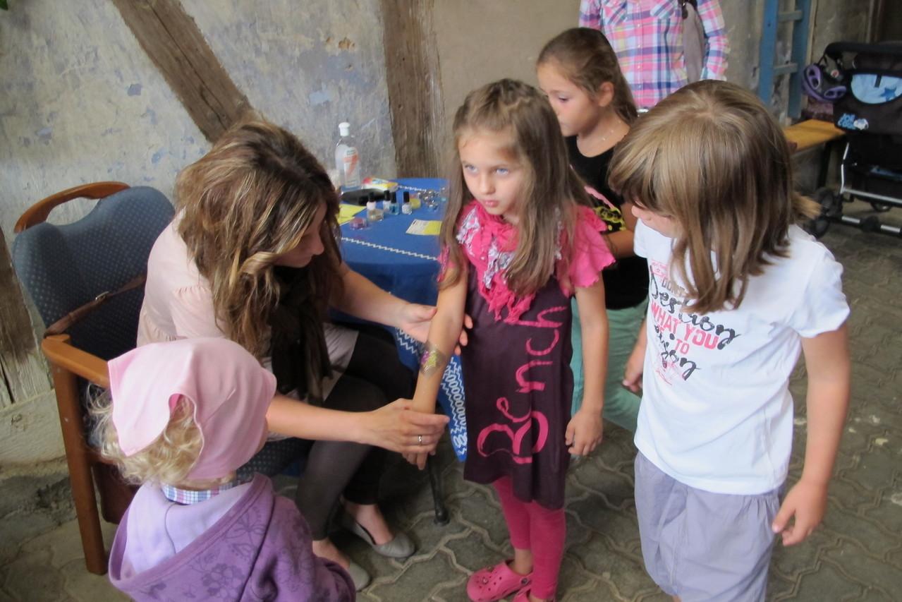 Anke Schaper schmückt die Kinder mit Tattoos