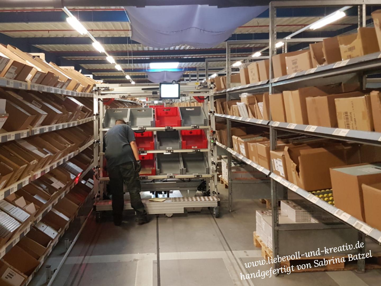 Der Roboter fährt automatisch durch die Packstraße. Die Boxen werden durch einen Mitarbeiter mit der Ware für die jeweilige Bestellung befüllt