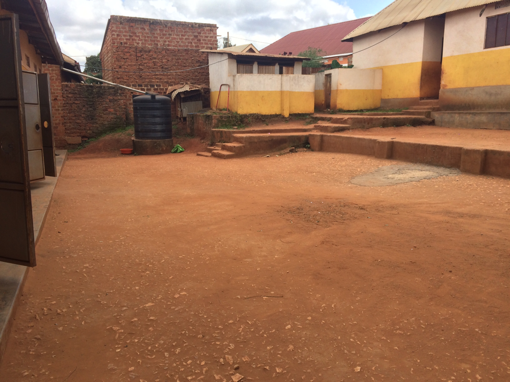 Der Hof im Vordergrund und das Toilettenhaus im Hintergrund