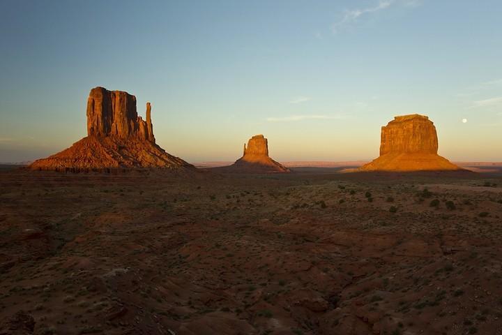 Sonnenuntergang im Monument Valley: West Mitten Butte, East Mitten Butte und Merrick Butte sowie Vollmond (von links nach rechts).