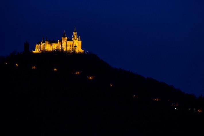 Blaue Stunde: Burg mit beleuchteter Auffahrt.