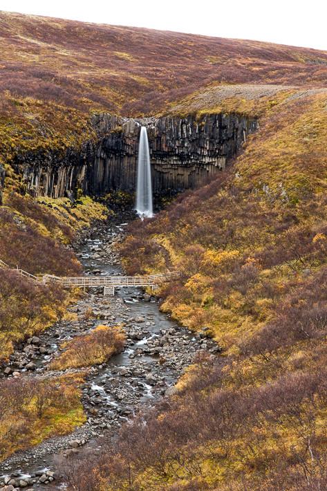 "Aussichtspunkt auf den Wasserfall ""Svartifoss"" mit Brücke über den Fluss."