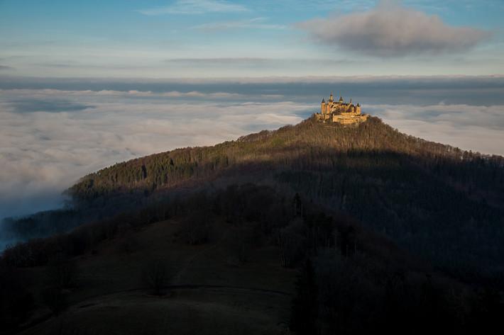 Die Burg Hohenzollern ragt aus dem Nebel heraus.