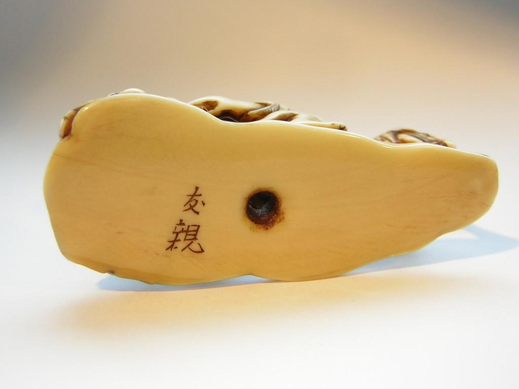Netsuke 1341 Katabori Samurai mit wilden Haaren und wehendem Gewand zu Pferd, dahinter zusammengebrochener Mann sich vor Schmerzen krümmend - alles auf Podest, Himotoshi im Boden  Edo Zeit ab 1860/65 signiert TOMOCHIKA  ca 49x27x14 mm 14,3 g  735,00 EUR