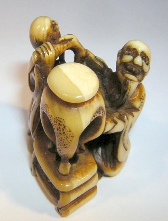 Netsuke 1135 Katabori zwei chin. Gelehrte einer mit Wanderstab und Schriftrolle neben Möbel, auf dem ein chinesischer Tisch steht - Himotoshi  Edo Zeit - mitte 19.Jh. um 1860  signiert vgl. Photoca 25x24x19 mm 10,3 g  Preis 515,00 EUR