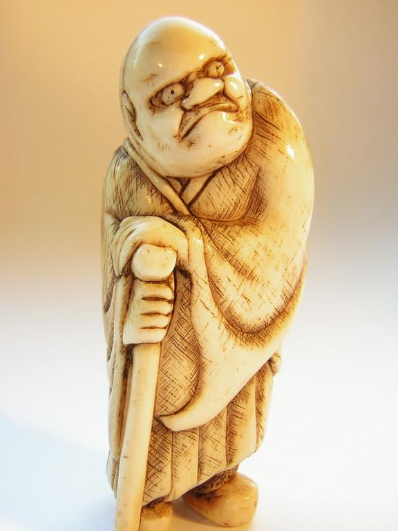 Netsuke 1357 Katabori Elfenbein stehender Mann auf Stock gelehnt mit Schwert am Rücken  Himotoshi  Edo Zeit -1.H. 19.Jh. um 1830-40  signiert: YASUHIDE  geschlossene materialbedingte Altersrisse ca 59x25x19 mm 23,5 g  Preis 1450,00 EUR