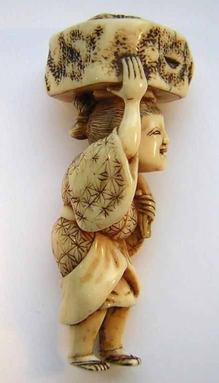 Netsuke 1152 Mann mit Baumstamm auf Kopf transportierend, kleines Utensilienbündel oben darauf -  Himotoshi  Edo Zeit - Mitte 19.Jh. um 1850  unsigniert  Elfenbein -  feine Ausarbeitung, schöne Gebrauchspatina  ca 59x15x24 mm 18,6 g 660,00 EUR