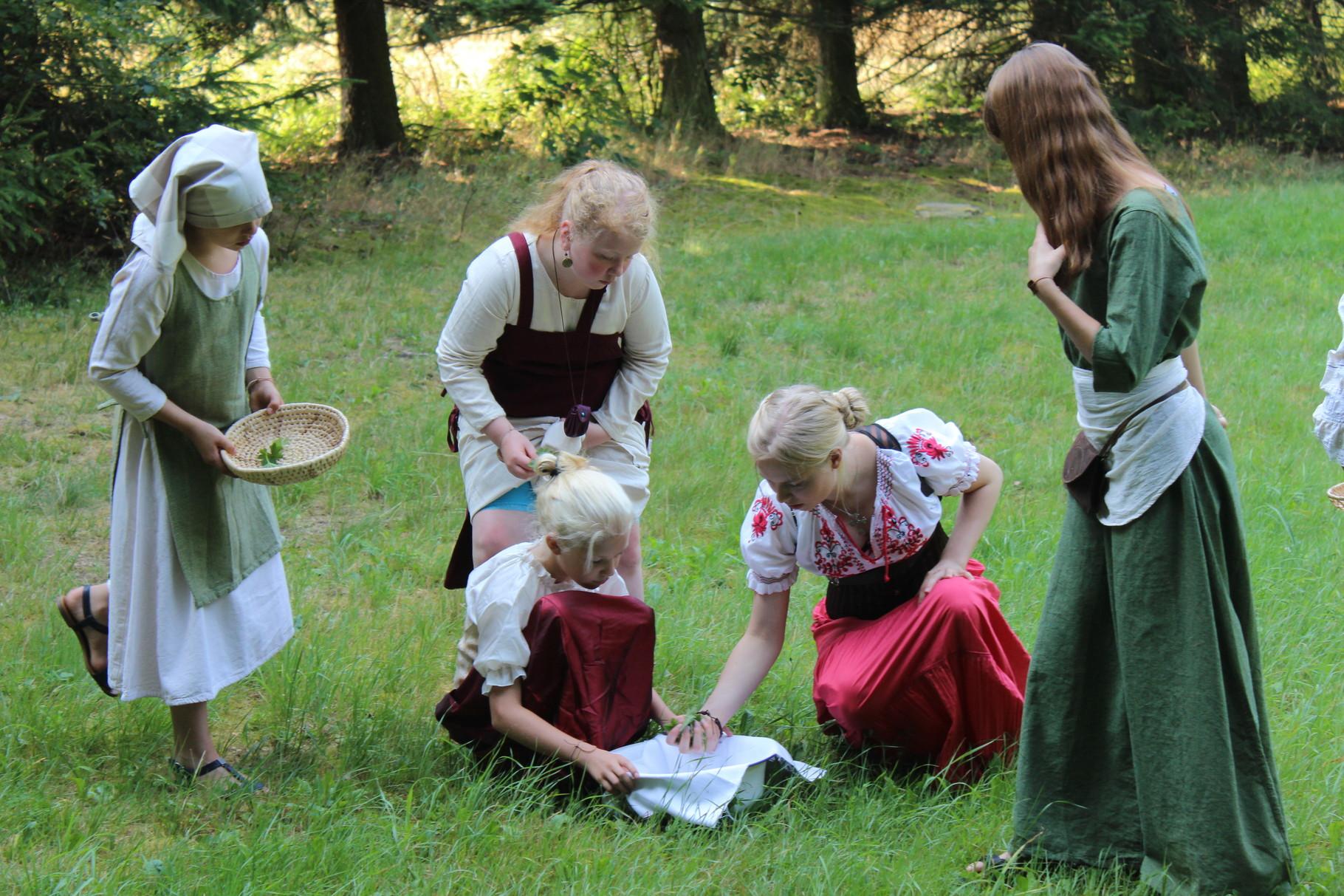 Das Wasser auf der Feuerstelle kocht schon fast, darum sammeln einige Bewohner die notwendigen Tee-Kräuter.