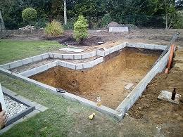 Loch für Koiteich baggern, Baggerarbeiten für Koiteich, Randsteine für die Randbefestigung des Koiteich