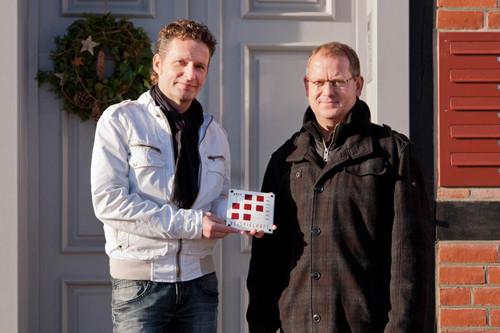 Markus Zillmann und Matthias Wieck halten die Plakette für das Theodor-Körner-Haus in der Hand