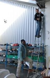 Abder et Jean-Pierre tirent une nouvelle ligne téléphonique pour l'atelier