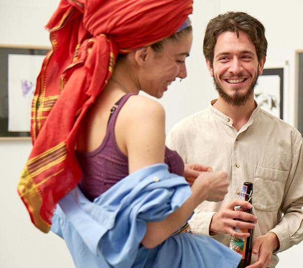 David Katzowicz im Gespräch mit einem seiner weiblichen Models, das einen riesigen, rote Turban auf dem Kopf trägt.uf dem K