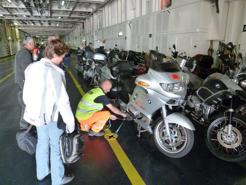 Andrée vérifie la fixation de la moto de Denis