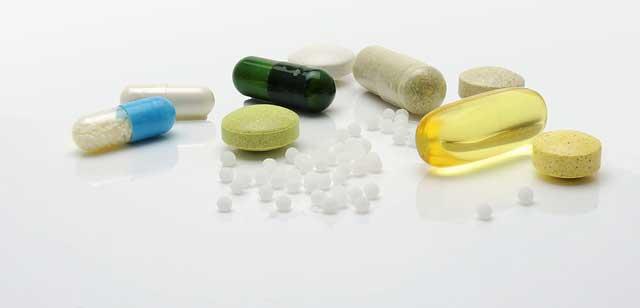 Schulmedizinische Medikamente und homöopathische Globuli nebeneinander auf einem weißen glatten Untergrund.