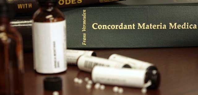 """Homöopathische Bücher (Materia Medica: """"Konkordanz""""), Arzneimittelflaschen und -röhrchen mit homöopathischen Mitteln. Arbeitsmittel des Homöopathen."""