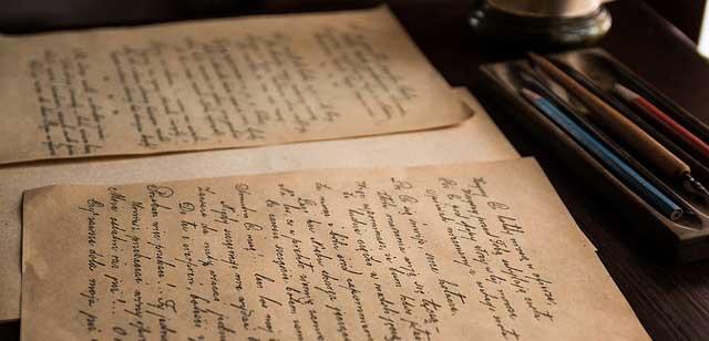 Alte Schriftstücke auf einem Schreibtisch mit Stiften.
