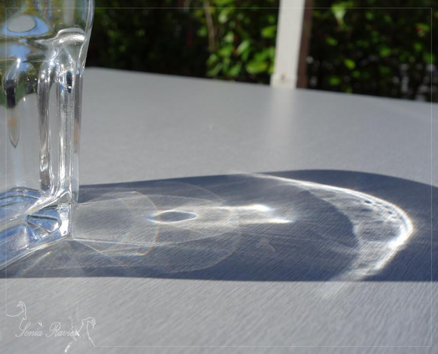 Reflet du soleil dans un verre d'eau posé sur une table    _  Riflesso del sole attraverso un bicchiere d'acqua su una tavola.
