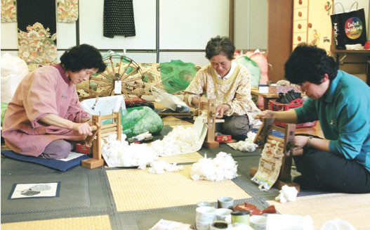 Volunteers removing seeds from cotton, 2003