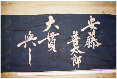 A drawn curtain donated by Ando Zentaro and Ohnuki Yoshi. Yoshi is perhaps a woman's name.