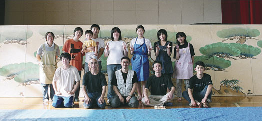 High school student volunteers help experts paint stage backdrops onto fusuma, 2003 and 2006