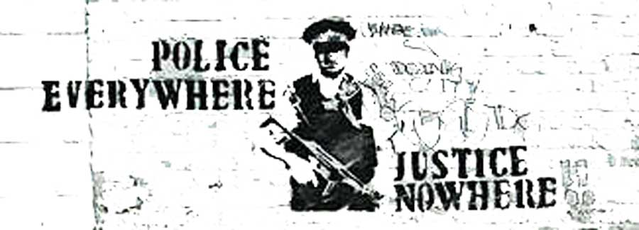 Photo of British culture: street graffiti saying 'Police everywhere, justice nowhere'.