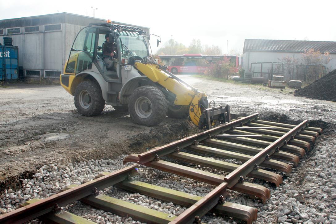 Ein Radlader der Firma EMB aus Schrozberg platziert ein Gleisjoch.